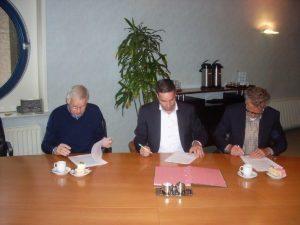 De ondertekenaars: midden wethouder Nieuwenhuizen namens de gemeente Langedijk, rechts Anne Oostenveld namens stichting Hart van Oudkarspel, links Dick Zuiderbaan namens Stichting Langedijker Verleden